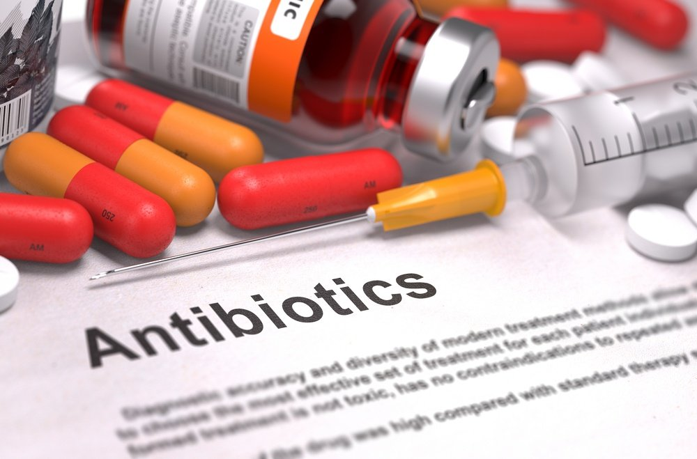 Antibiotics - Printed Diagnosis with Blurred Text. On Background of Medicaments Composition - Red Pills, Injections and Syringe..jpeg