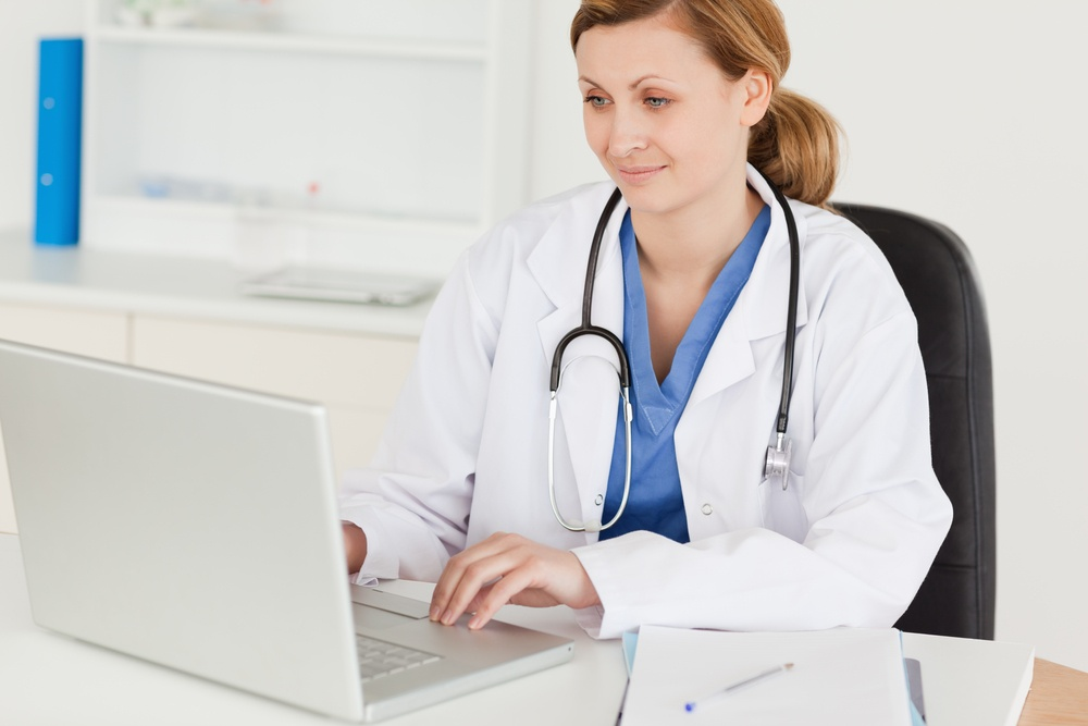 Attractive female doctor working on her laptop in her office.jpeg