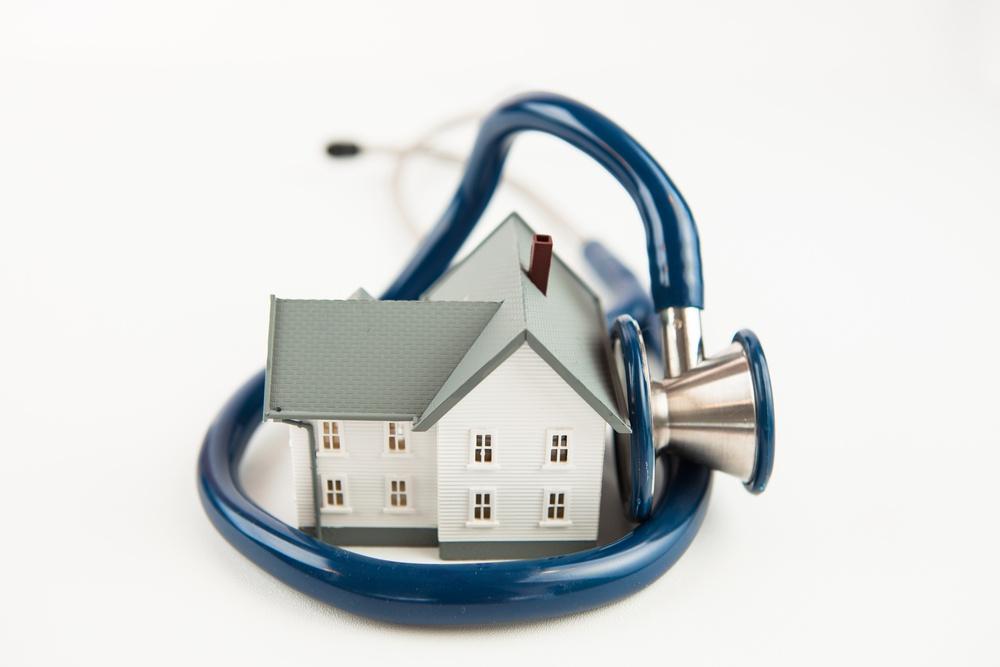 Blue stethoscope wrapped aroud tiny house model on white background
