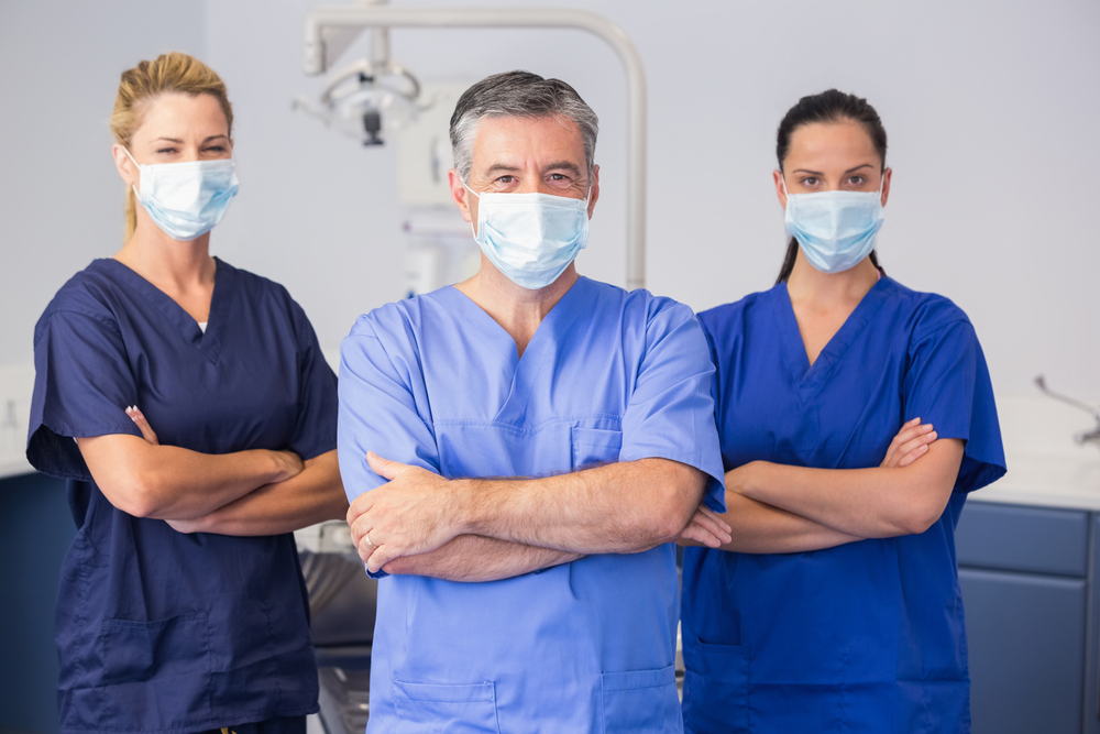 Co-workers wearing surgical mask with arms crossed in dental clinic