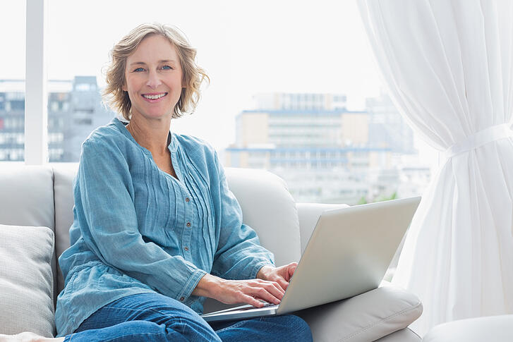 woman sitting on her couch using laptop smiling at camera at home in the sitting room