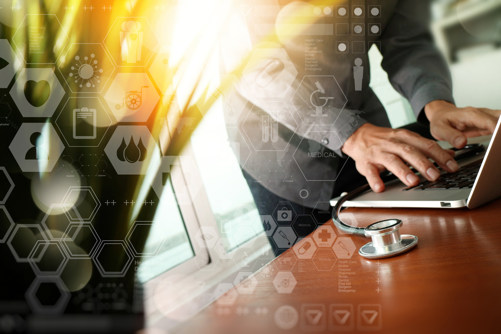 Doctor working at workspace with laptop computer in medical workspace office and digital medical layers diagram with green plant foreground-1