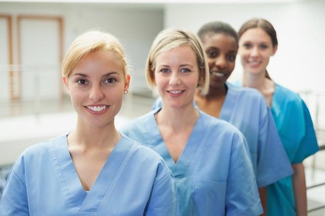 Female nurse looking at camera in hospital hallway.jpeg