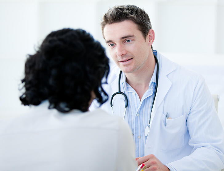 Doctor talking with his patient for the annual check-up in the hospital