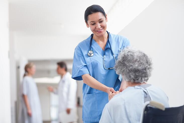 Nurse standing next to a patient while holding her hands in hospital ward.jpeg