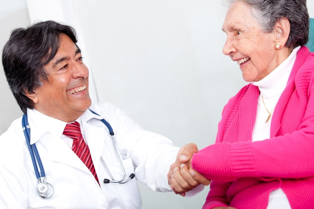 Old woman handshaking with a friendly doctor