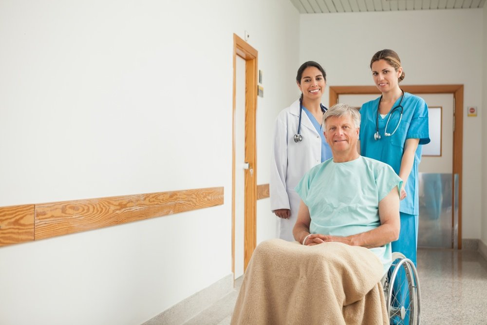 Patient in a wheelchair next to nurses in hospital