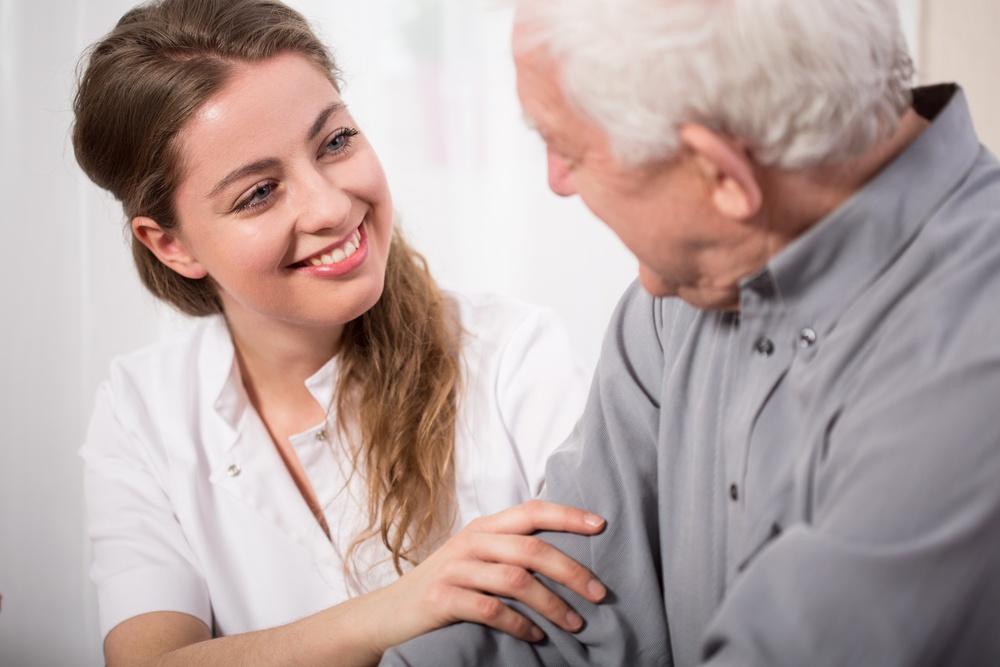 Picture of smiling nurse assisting senior man-1