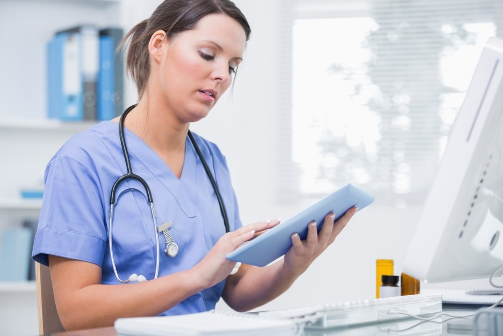 Side view of young female surgeon using digital tablet in front of computer at desk in clinic.jpeg