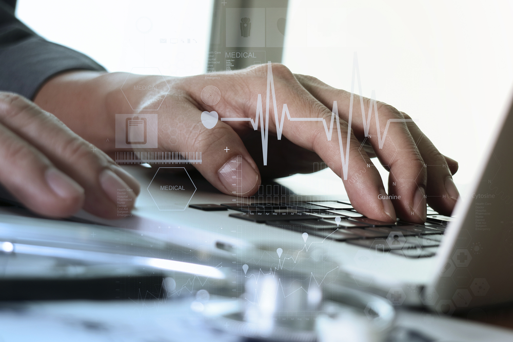 close up of Medicine doctor hand working with modern computer and medical diagram layers on wooden desk as medical concept