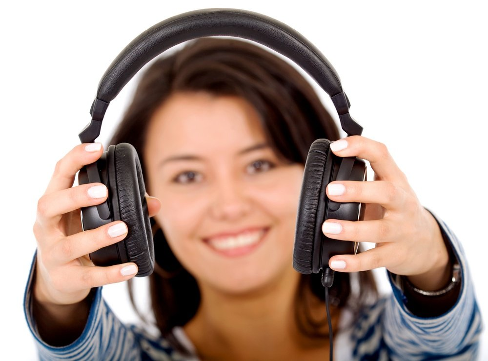 girl holding headphones and smiling isolated over a white background